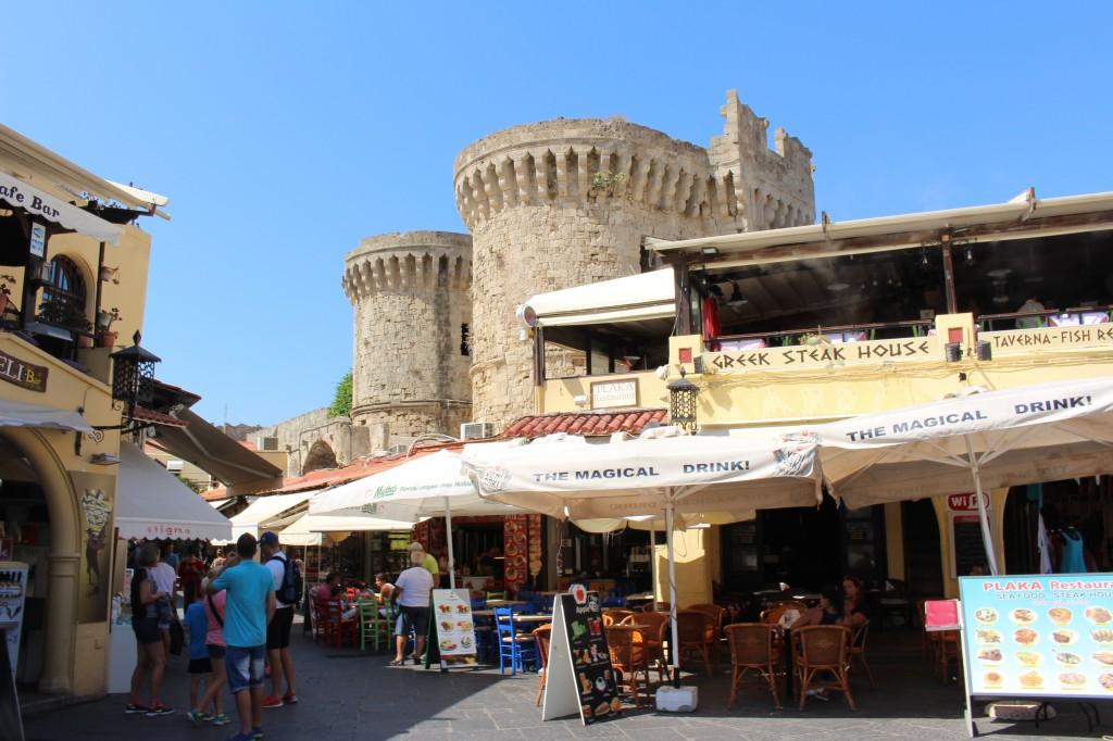 A busy shopping street with a historic background in Rhodes.